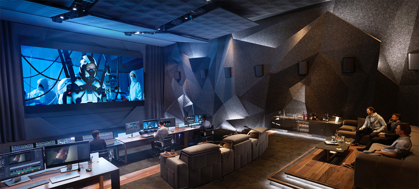 A very expensive looking cinema edit suite with multiple edit stations, viewing couches and huge cinema wall at the front.